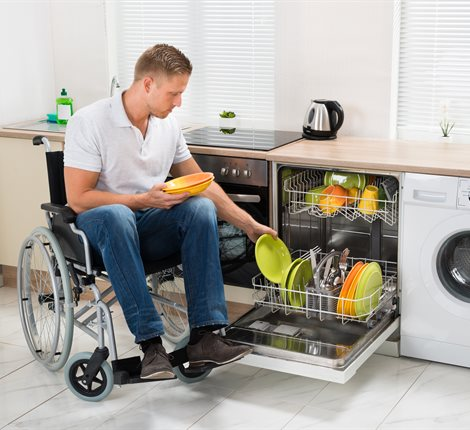 Man on a wheelchair using an accessible kitchen and loadiing a dishwasher
